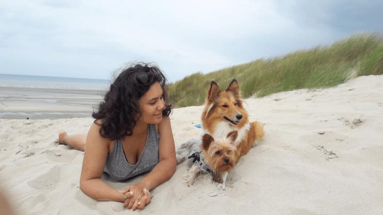 Une fille sur la plage avec ses deux chiens