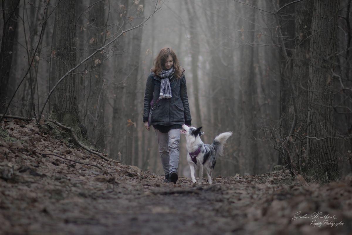 Emilie marche avec son chien au pied dans les bois