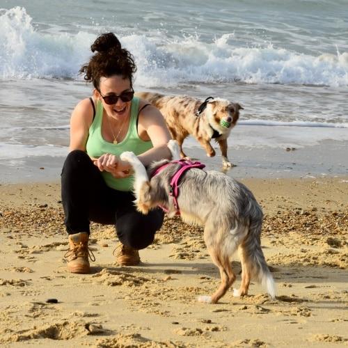 une jeune femme pratique le dog da,cing avec un border collie sur la plage